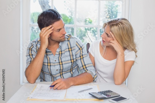 Worried couple with financial documents and calculator
