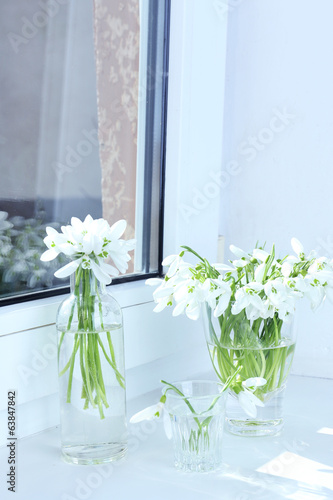Beautiful bouquets of snowdrops in vases on windowsill