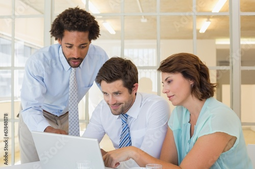 Concentrated business people using laptop at office
