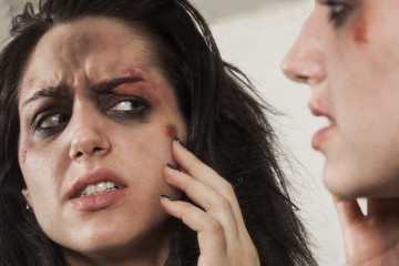 Beaten up girl looking in the mirror