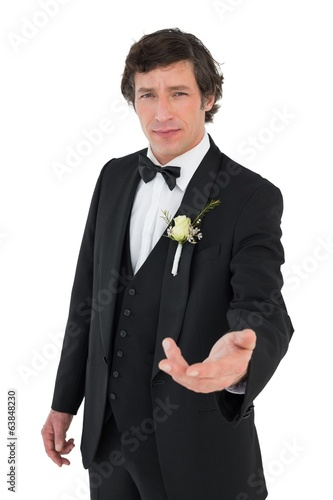 Confident groom in tuxedo offering hand