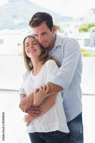 Loving young man embracing woman at home