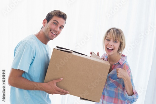 Happy couple carrying cardboard box in new house