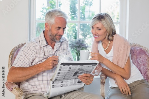 Couple reading newspaper while drinking coffee