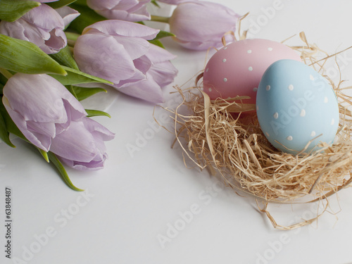 Easter nest with two eggs and bouqet tulips
