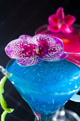 Blue swimming pool Cocktail with caviar and flower petals