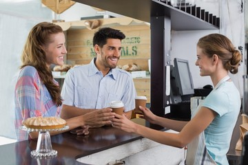 Waitress giving coffee to a couple at coffee shop