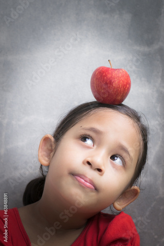 little cute girl with red apple on hers head