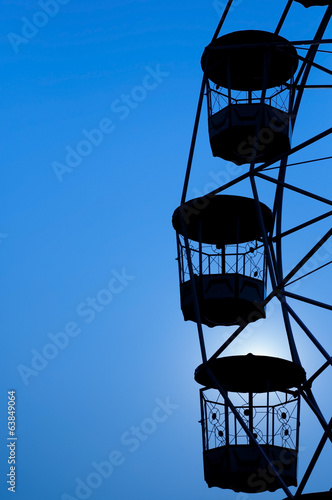 Ferris wheel silhouette in blue sky.