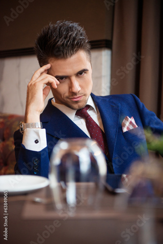 canvas print picture Successful businessman sitting at the table of the restaurant
