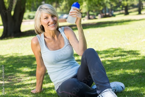 canvas print picture Relaxed woman holding water bottle in park