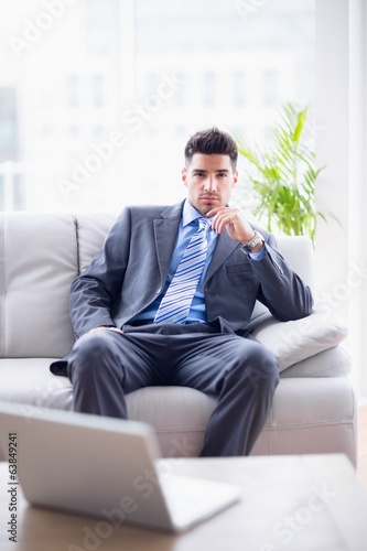 Serious businessman sitting on the couch looking at camera