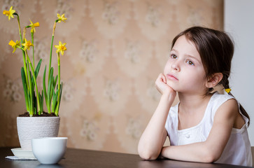 Thoughtful preschooler girl in the kitchen