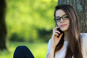 Jolie jeune femme téléphonant assise contre un arbre.
