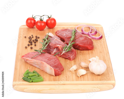 Raw beef steaks on a wooden cutting board.