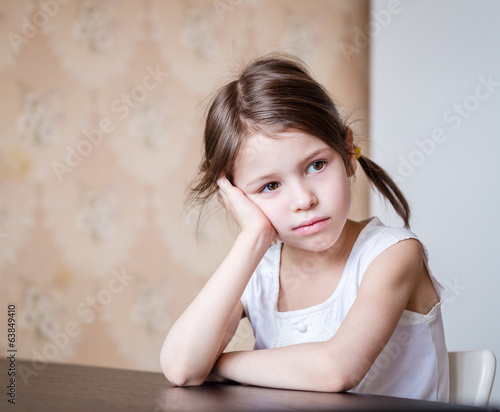 Dissatisfied preschooler girl in the kitchen
