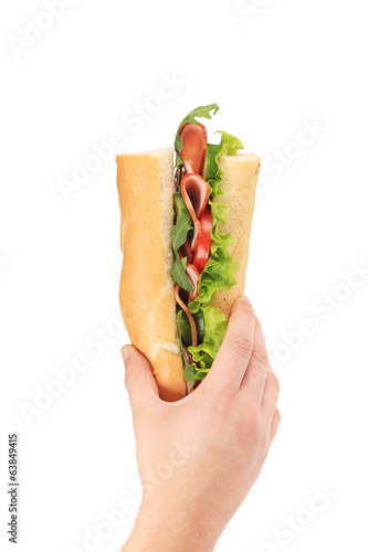 Hand holding sandwich with ham and tomato slices.