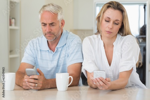 Bored couple sitting at the counter texting