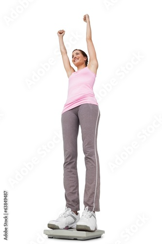 Young woman cheering on weight scale