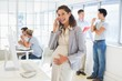 Pregnant businesswoman talking on phone with team behind her