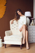 portrait of beautiful woman sitting on white arm-chair