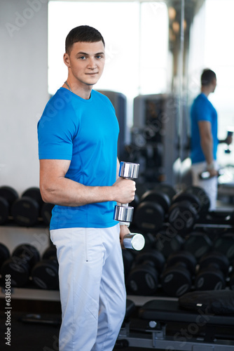 young guy is engaged with a dumbbell