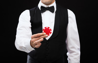 dealer holding red poker chip