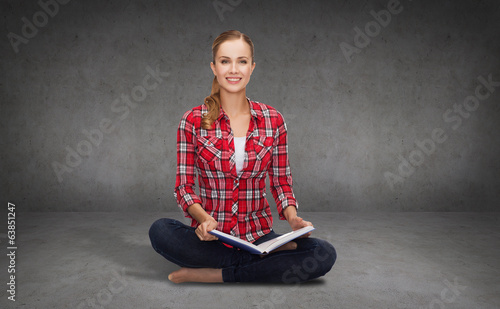 smiling young woman sittin on floor with book