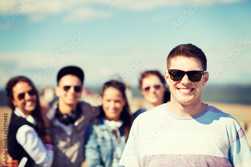 teenager in shades outside with friends