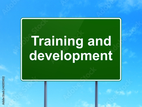 Education concept: Training and Development on road sign