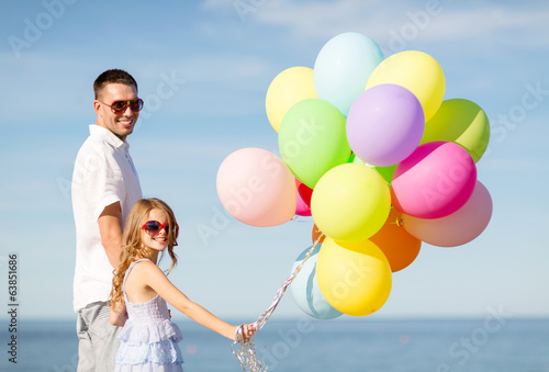happy father and daughter with colorful balloons