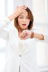 stressed businesswoman looking at wrist watch