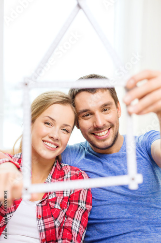 smiling couple with house from measuring tape