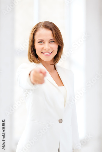 smiling businesswoman pointing finger at you