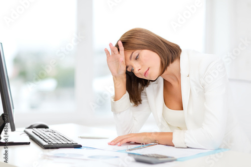 tired businesswoman with computer and papers
