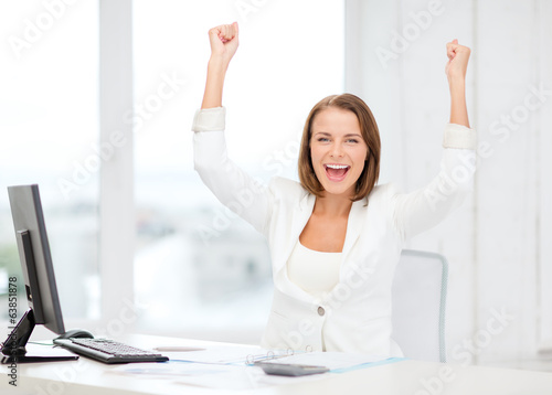 happy businesswoman with computer in office