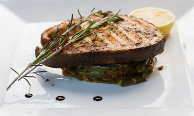 Grilled steaks of fresh fish with lemon and rosemary
