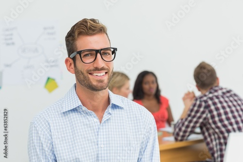 canvas print picture Handsome designer smiling at camera with colleagues behind him