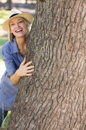 Woman hiding behind tree trunk