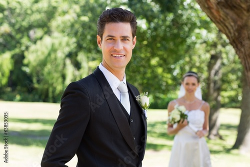 Confident groom with bride in background at garden