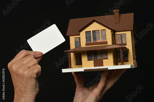 Hand holding miniature house and blank card