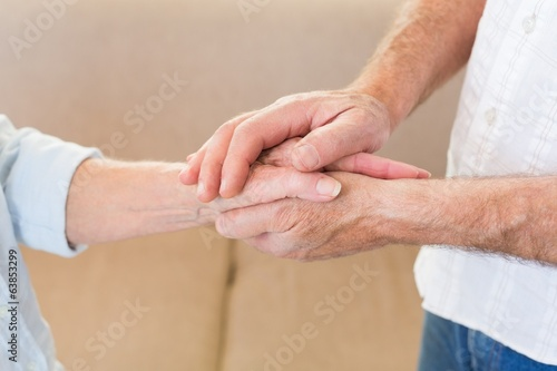 Retired couple touching hands