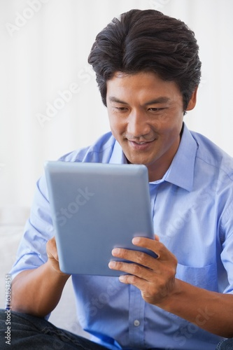 Happy man sitting on couch using tablet
