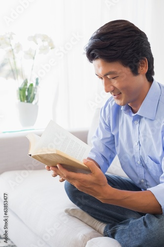Happy man sitting on couch reading