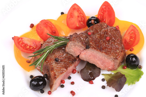 Beef steaks with rosemary and tomatoes.