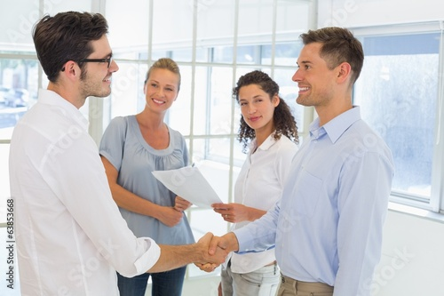 Casual businessmen shaking hands and smiling