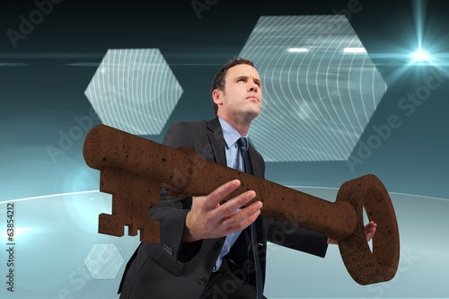 Composite image of businessman carrying large key