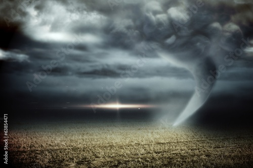 Stormy sky with tornado over field