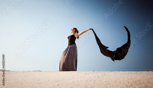 arabian woman with long cloth at desert on windy day