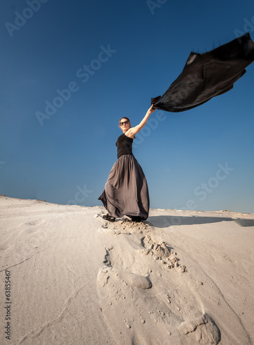 woman in long dress holding long cloth on sand dune